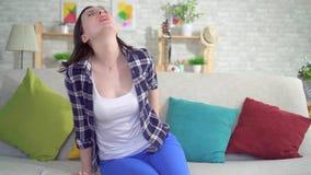 La femme s'asseyant sur le divan, éprouvant la douleur et le malaise des hémorroïdes se ferment  banque de vidéos
