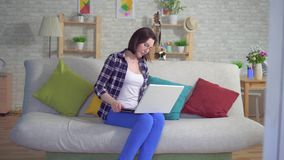 La femme s'asseyant sur le divan travaillant sur un ordinateur portable éprouve la douleur et le malaise des hémorroïdes banque de vidéos