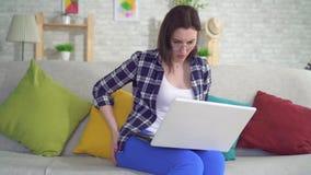 La femme s'asseyant sur le divan travaillant sur un ordinateur portable éprouve la douleur et le malaise des hémorroïdes se ferme banque de vidéos
