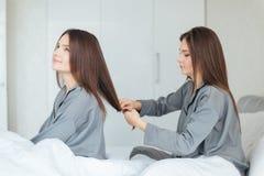 La femme s'asseyant sur le lit et balayant ses sistes jumellent des cheveux Images stock
