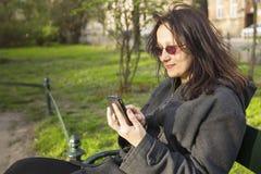La femme s'asseyant sur un banc de parc parle par le téléphone Images stock