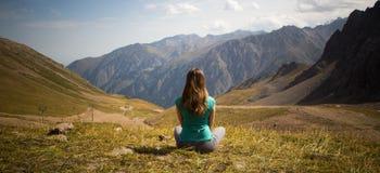 La femme s'asseyent dans le style de yoga et examinent la distance Photographie stock