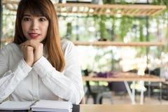 La femme s'asseyent en café étudiante avec le carnet dans le café photos stock