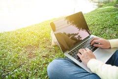 La femme s'asseyent pour utiliser l'ordinateur portable au parc avec la lumière d'or Photos libres de droits