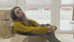 La femme s'assied à l'intérieur de la boîte vide et de prévoir une nouvelle vie dans la nouvelle maison banque de vidéos