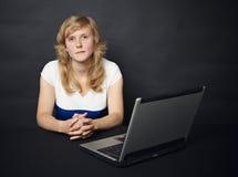 La femme s'assied à la table avec l'ordinateur Image stock