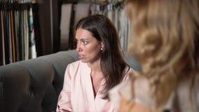 La femme s'assied avec le client sur un sofa et parle des détails de contrat clips vidéos