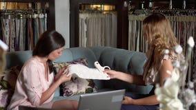 La femme s'assied avec le client sur un sofa et parle des détails de contrat La femme aide à choisir la conception de la salle banque de vidéos