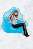 La femme s'assied dans un fauteuil à l'extérieur en hiver Image libre de droits