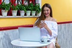 La femme s'assied dans une brasserie et travaille à l'ordinateur portable et au smartphone photographie stock