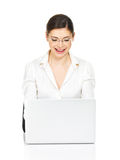 La femme s'assied de la table avec l'ordinateur portable dans la chemise blanche Photo libre de droits