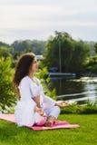 La femme s'assied en position de lotus image libre de droits