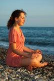 La femme s'assied et méditation à terre de mer Image stock