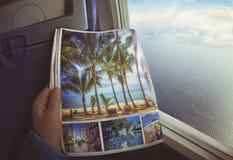 La femme s'assied par la fenêtre sur un avion avec la magazine dans des mains images stock