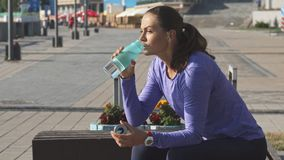 La femme s'assied sur la branche, boit l'eau et regarde fixement dans la distance banque de vidéos