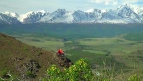 La femme s'assied sur la colline et regarde des montagnes de neige banque de vidéos