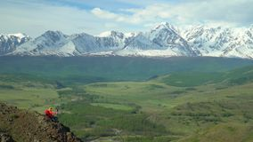 La femme s'assied sur la colline et regarde des montagnes de neige clips vidéos