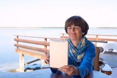 La femme s'assied sur la véranda sur le bord de mer, utilisant un comprimé Photographie stock