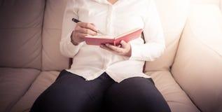 La femme s'assied sur un sofa et écrit des notes dans un carnet Photos stock