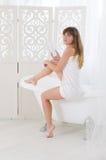 La femme s'assied sur une baignoire Image stock