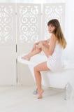 La femme s'assied sur une baignoire Photographie stock libre de droits