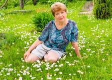 La femme s'assied sur une clairière avec des fleurs de marguerite photo libre de droits