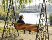 La femme s'assied sur une oscillation Femme d'une cinquantaine d'années seule sur une oscillation Image stock