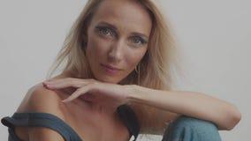 La femme 30s blonde pose dans le studio à l'appareil-photo banque de vidéos