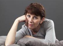 La femme 50s décontractée de sourire s'est étendue sur les coussins gris Images stock