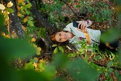 La femme s'est élevée dans un arbre causant et textotant au téléphone intelligent Photo libre de droits