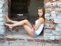 La femme s'est assise pour avoir un reste sur des ruines de ville Photos stock