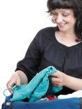 La femme s'est entassée complètement des vêtements et du sac d'épaule d'isolement Photographie stock libre de droits