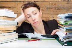La femme s'est fatiguée du travail et de l'étude à côté de la pile Images libres de droits