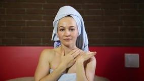La femme s'est habillée dans une crème de visage de diffusions de serviette de bain Soin de peau peau quotidienne de massages fac banque de vidéos