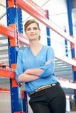 La femme sûre d'affaires détendant à côté de rayonnent des supports dans l'entrepôt Image libre de droits