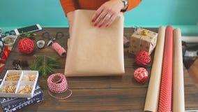 La femme s remet envelopper le cadeau de Noël sur le fond en bois foncé clips vidéos