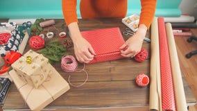La femme s remet envelopper le cadeau de Noël sur le fond en bois foncé banque de vidéos