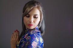 La femme samouraï s'est habillée dans la robe en soie asiatique colorée traditionnelle de modèle de fleur, tenant des mains ensem Images stock
