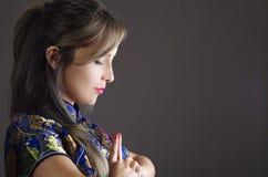 La femme samouraï s'est habillée dans la robe en soie asiatique colorée traditionnelle de modèle de fleur, tenant des mains ensem Photo libre de droits