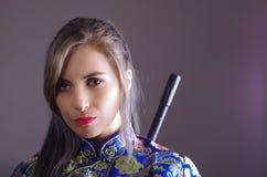 La femme samouraï s'est habillée dans la robe en soie asiatique colorée traditionnelle de modèle de fleur, tenant le bras au-dess Image stock