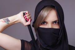La femme samouraï s'est habillée dans le noir avec le visage assorti de bâche de voile, bras de participation sur le dos derrière Photo libre de droits