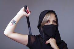 La femme samouraï s'est habillée dans le noir avec le visage assorti de bâche de voile, bras de participation sur le dos derrière Photos stock
