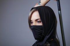La femme samouraï s'est habillée dans le noir avec le visage assorti de bâche de voile, bras de participation sur le dos derrière Image stock