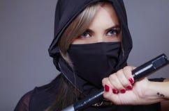 La femme samouraï s'est habillée dans le noir avec le visage assorti de bâche de voile, main de participation sur l'épée faisant  Image libre de droits