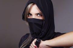 La femme samouraï s'est habillée dans le noir avec le visage assorti de bâche de voile, main de participation sur l'épée faisant  Image stock