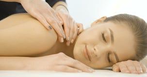 La femme sarisfied attirante apprécie le massage avec les yeux fermés dans le salon de station thermale Appareil-photo mobile au- banque de vidéos