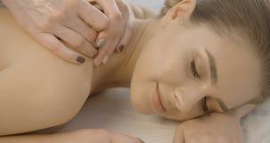 La femme satisfaisante de sourire avec la porcelaine pèlent et maquillage naturel regardant in camera pendant le massage dans le  banque de vidéos