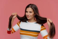 La femme satisfaite tient ses longs cheveux inquiétés, sourires doucement, habillés dans le pullover rayé blanc, regarde la camér photo libre de droits