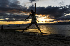 La femme sautant au coucher du soleil Photographie stock libre de droits