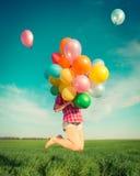 La femme sautant avec le jouet monte en ballon au printemps le champ Image stock